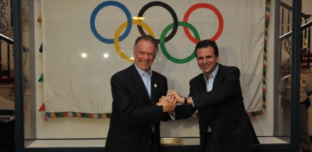 Carlos Arthur Nuzman (e) e Eduardo Pares posam ao lado da bandeira olímpica no Palácio da Cidade