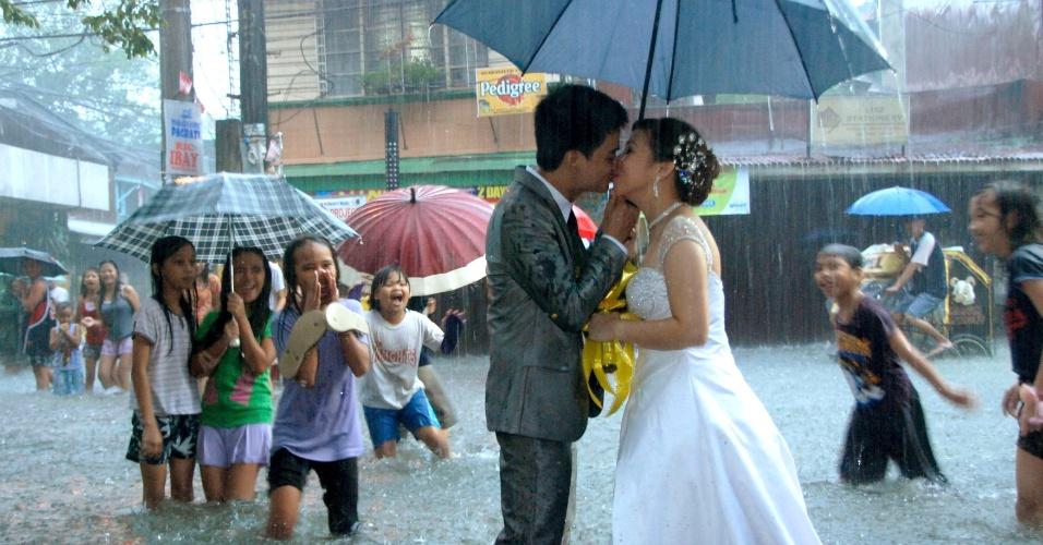 O casal de filipinos Ramoncito Camp e Hernelie Ruazol Campo, que mesmo com as inundações que atingem a capital Manila, se casaram no dia 8 de agosto