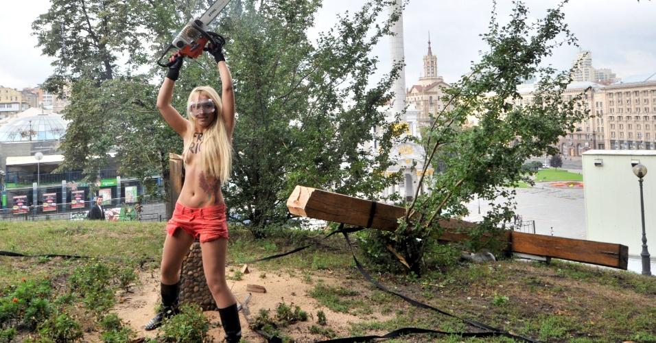 17.ago.2012 - Ativista do grupo feminista ucraniano Femen segura uma motosserra após cortar uma cruz, erguida em memória às vítimas da repressão policial em Kiev, na Ucrânia. O protesto ocorreu em apoio à banda russa de punk Pussy Riot. Três integrantes do grupo foram consideradas culpadas de vandalismo pelo tribunal de Khamovniki nesta sexta. Elas foram sentenciadas a dois anos de prisão