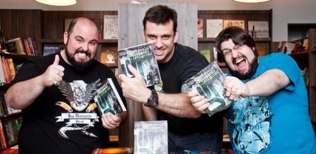 """Deive """"Azaghal"""" Pazos (esquerda), o escritor Eduardo Sphor (meio)  e Alexandre """"Jovem Nerd"""" Ottoni (direita) com obras da Nerdbooks - Divulgação"""