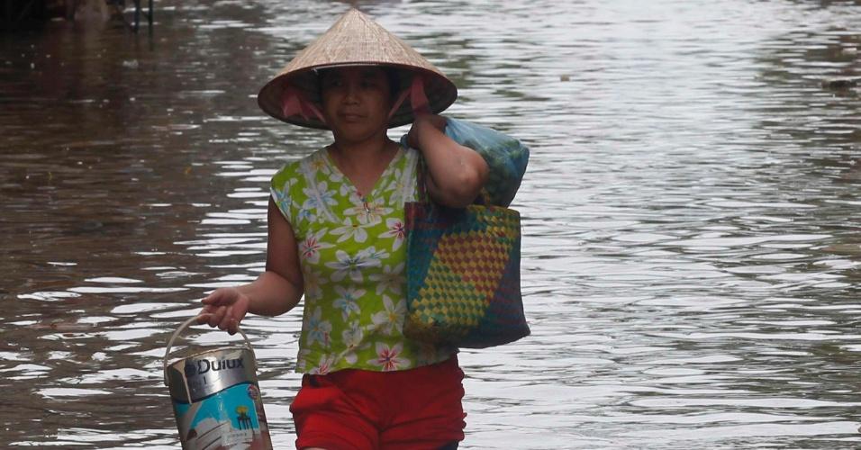 """18.ago.2012 - Mulher anda por rua inundada em Hanói, no Vietnã. Pelo menos quatro pessoas morreram após a passagem da tempestade tropical """"Kai-Tac"""", que levou cheias e fortes ventos ao norte do país"""