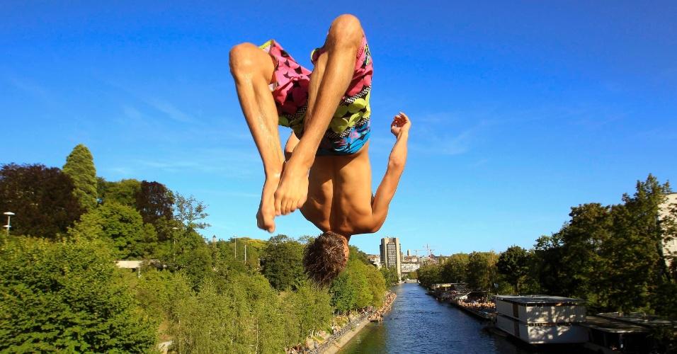 18.ago.2012 - Um homem salta de uma ponte no rio Limmat, em Zurique, Suíça, durante sol característico do verão no país. A previsão é que a onda de calor dure até 22 de agosto