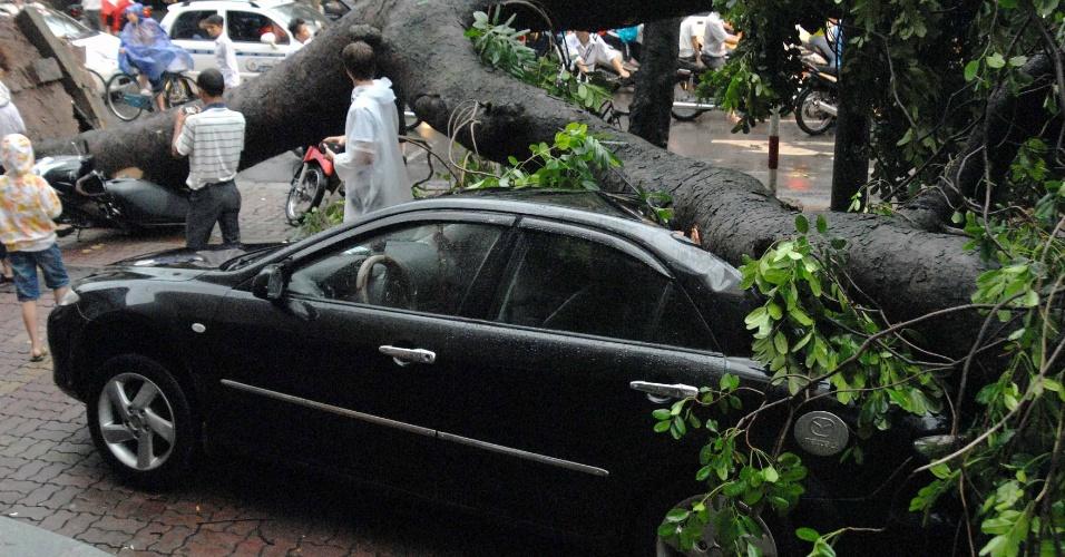 """18.ago.2012 - Vietnamitas observam árvore em cima de carro em Hanói, no Vietnã. Pelo menos quatro pessoas morreram após a passagem da tempestade tropical """"Kai-Tac"""", que levou inundações e fortes ventos ao norte do país"""