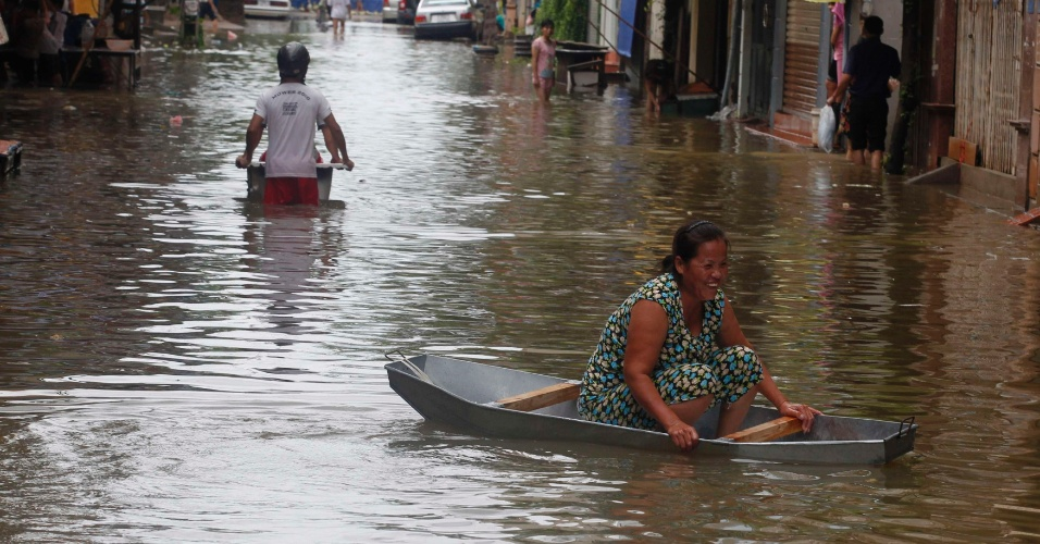"""18.ago.2012 - Vietnamitas recorrem a barcos para se locomoverem por rua inundada em Hanói, no Vietnã. Pelo menos quatro pessoas morreram após a passagem da tempestade tropical """"Kai-Tac"""", que levou inundações e fortes ventos ao norte do país"""