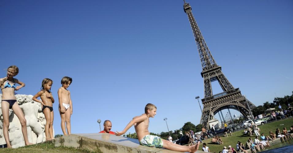 18.ago.2012 ? Crianças improvisam um escorregador nas Fontes Trocadero, em Paris (França), para aproveitar o calor do verão europeu