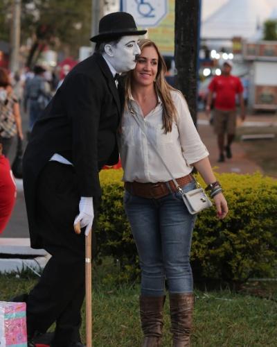 18.ago.2012 - Mulher tira foto com imitador de Charles Chaplin durante o terceiro dia da Festa do Peão de Barretos, no interior de São Paulo