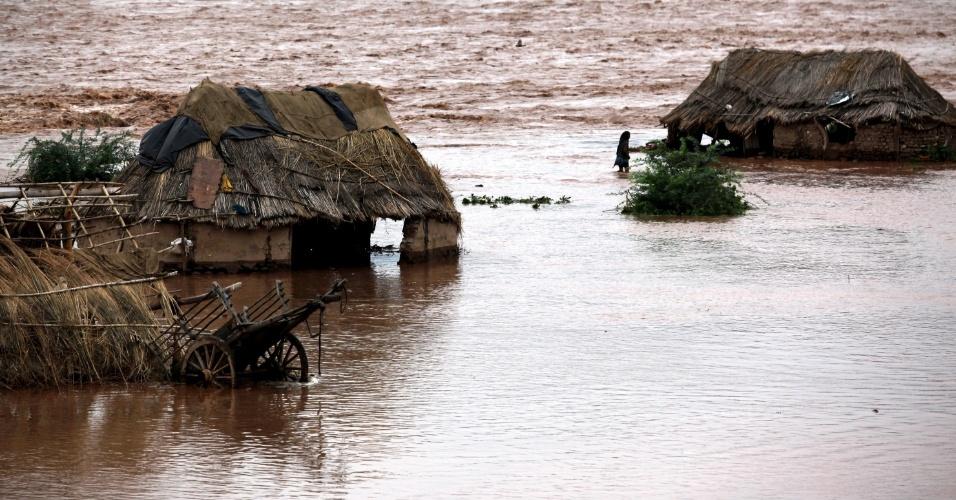 19.ago.2012 - Indiano caminha para sua casa, inundada durante enchente do rio Tawi, nos arredores de Jammu, na Índia