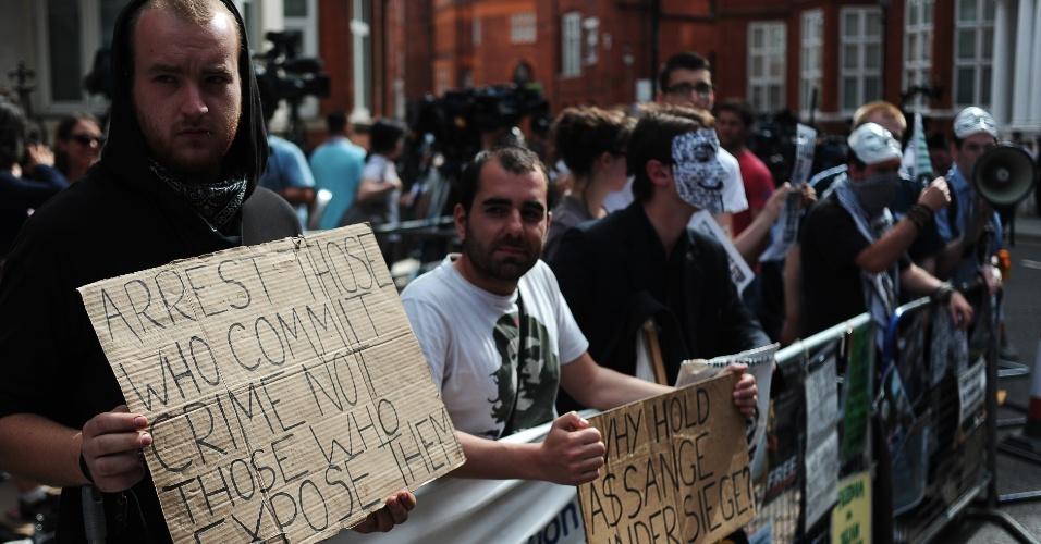 19.ago.2012 - Ingleses exibem cartazes de apoio em frente à Embaixada do Equador em Londres, na Inglaterra, durante o primeiro discurso de Julian Assange, fundador do WikiLeaks, após o refúgio