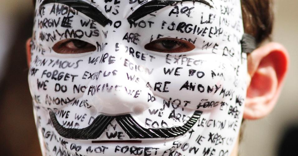 19.ago.2012 - Manifestante mascarado aguarda o fundador do WikiLeaks, Julian Assange, que falará com a imprensa, em frente à embaixada do Equador em Londres, neste domingo (19). Enquanto o impasse diplomático entre Reino Unido e Equador não é resolvido, Assange se refugiou na Embaixada do Equador para evitar ser preso