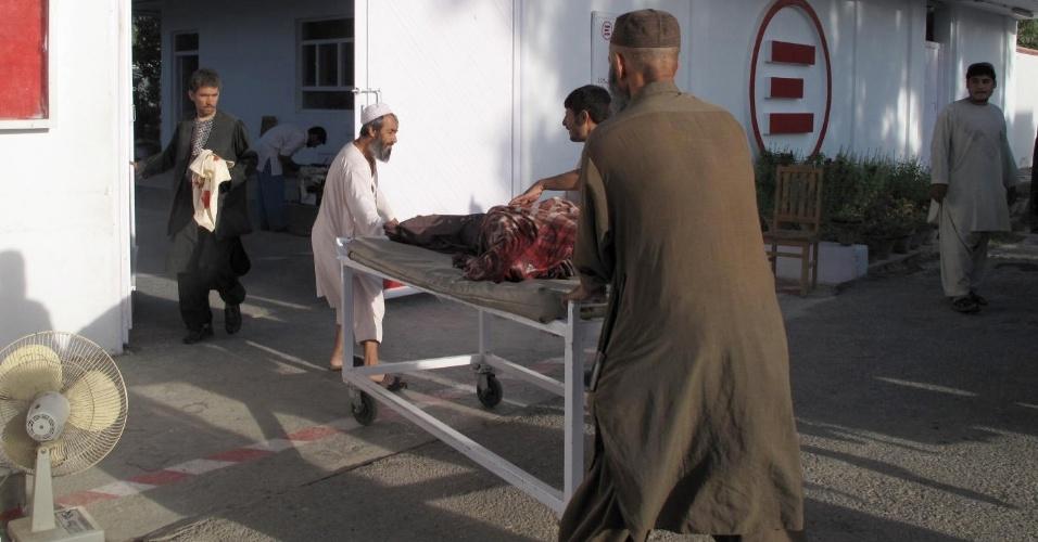 19.ago.2012 - Médicos afegãos socorrem homem ferido para hospital neste domingo (19), em Lashkar Gah, na província de Helmand, no Afeganistão
