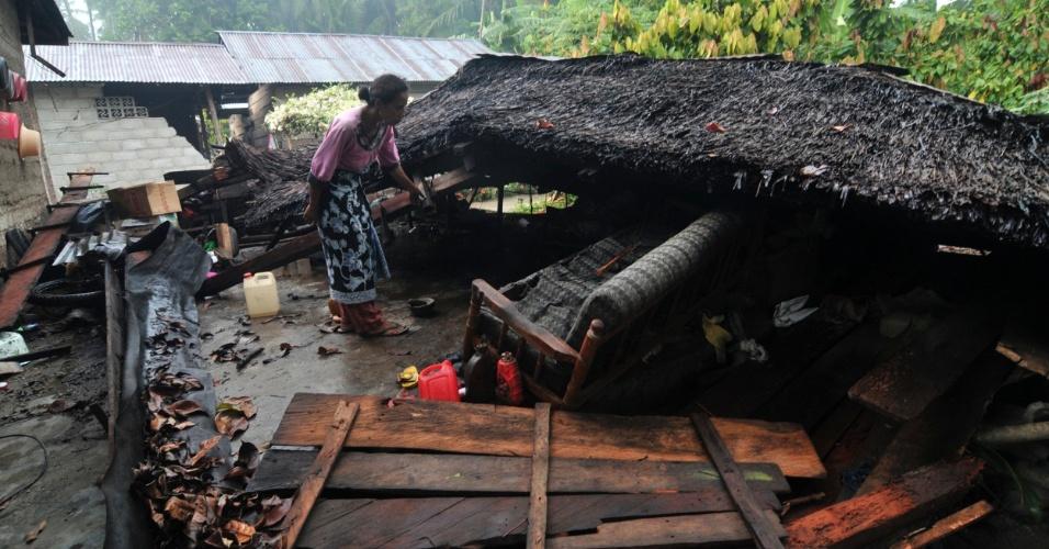 19.ago.2012 - Mulher inspeciona sua casa destruída por um terremoto na vila de Tuva, na província de Sulawesi, na Indonésia. Ao menos três pessoas morreram e 12 ficaram feridas