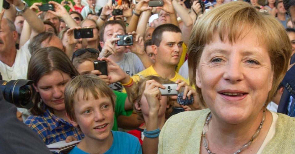 19.ago.2012 - Multidão cerca a chanceler alemã, Angela Merkel, durante dia em que a chancelaria do país abre as portas para receber visitantes