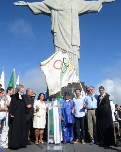 19.ago.2012 - O prefeito do Rio de Janeiro, Eduardo Paes, o presidente do Comitê Olímpico Brasileiro, Carlos Arthur Nuzman, e o arcebispo do Rio de Janeiro, dom Orani Tempesta, levam a bandeira olímpica ao Cristo Redentor, na capital fluminense, neste domingo (19)