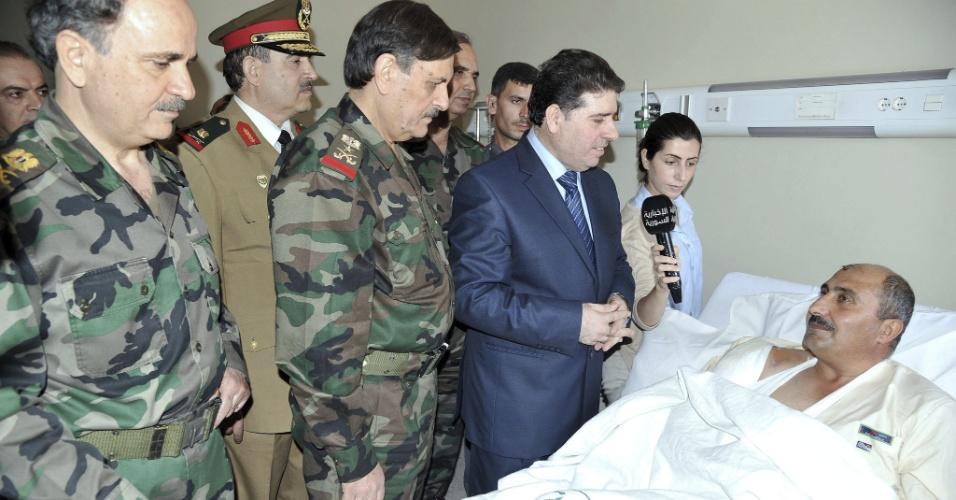 19.ago.2012 - O primeiro-ministro da Síria, Wael al Halgi (de terno), e o ministro da Defesa, Fahd  Jassem Freej (fardado, no centro da imagem), visitam soldados feridos no hospital de Damasco, capital síria, para felicitações do Eid al-Fitr, festa que marca o fim do Ramadã