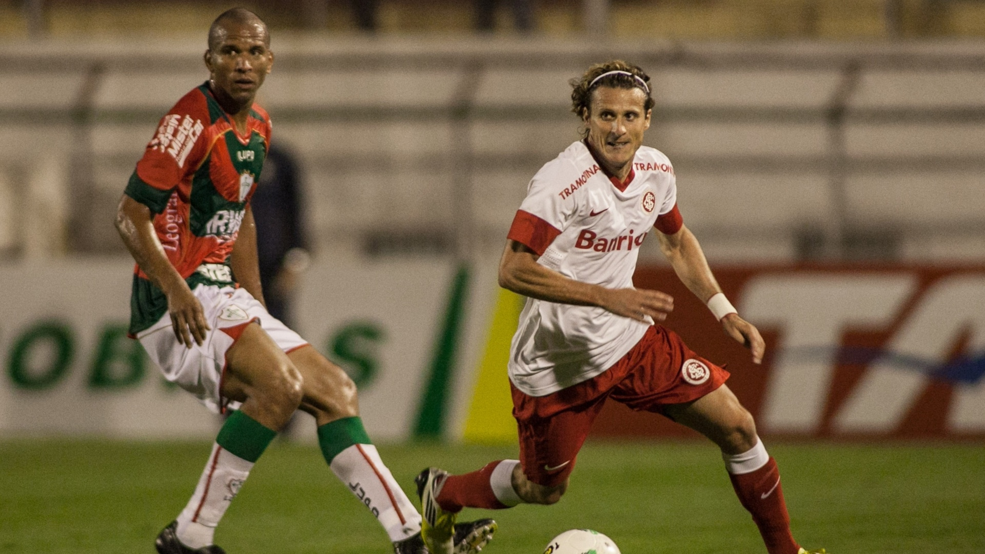 Forlán conduz a bola e passa pela marcação de jogador da Portuguesa durante empate no Canindé