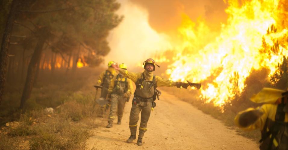 20.ago.2012 - Bombeiro gesticula enquanto trabalha na contenção de um incêndio florestal em Tabuyo del Monte, na Espanha