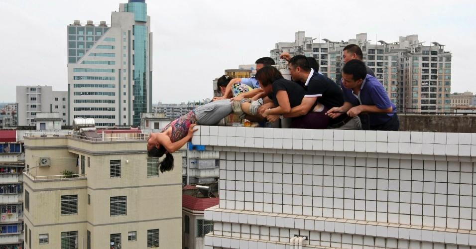 20.ago.2012 - Foto tirada no dia 14 de agosto e divulgada nesta segunda-feira (20) mostra parentes impedindo que uma mulher cometesse suicídio em Zhanjiang, na China. Segundo a imprensa local, ela tentou pular do prédio após matar o sobrinho durante uma disputa familiar