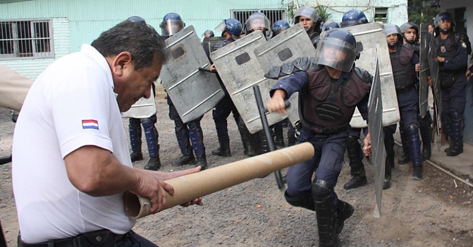 20.ago.2012 - Funcionário do Tesouro do Paraguai se confronta com policiais durante um protesto para pedir aumento salarial em Assunção, capital paraguaia