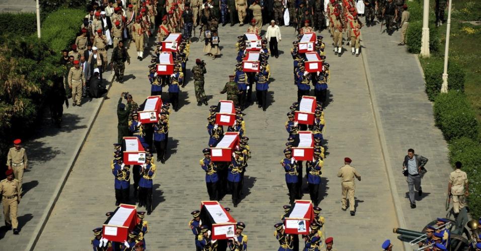20.ago.2012 - Guardas levam caixões com vítimas de um ataque a bomba em Sana, no Iêmen, ocorrido no sábado (18). O ataque, cuja autoria foi atribuída à Al Qaeda, mas sem confirmação do grupo terrorista, matou pelo menos 14 policiais