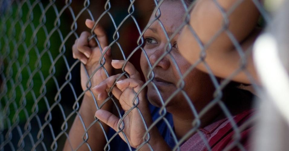 20.ago.2012 - Mulher aguarda em grade na prisão de Yare, na Venezuela