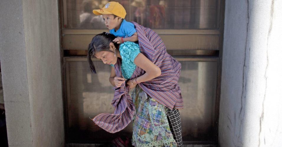 20.ago.2012 - Mulher indígena carrega o filho nas costas enquanto se prepara para ficar em frente a um tribunal na Cidade da Guatemala