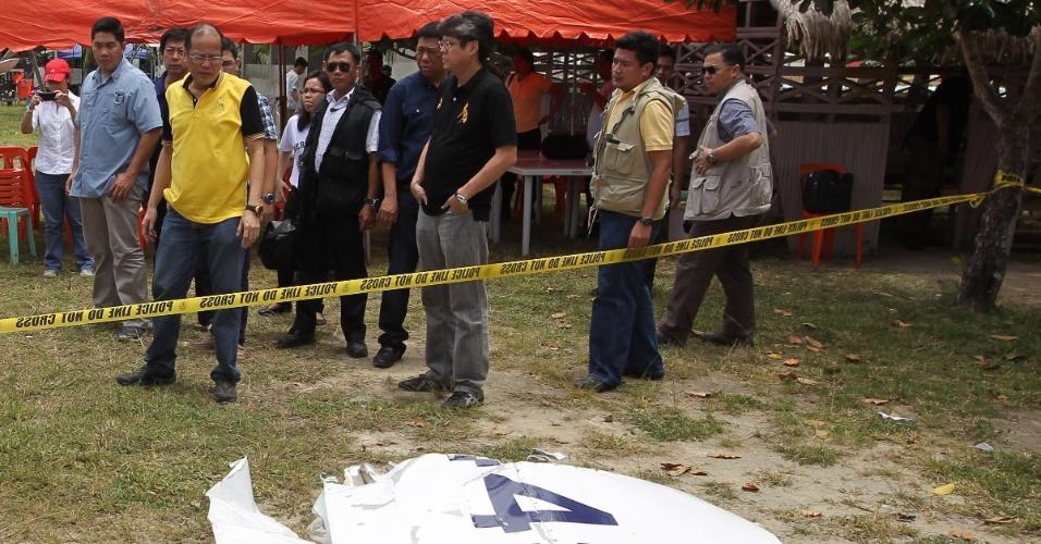 20.ago.2012 - O presidente das Filipinas, Benigno Aquino, observa uma parte da fusilagem do avião que caiu com o ministro do Interior das Filipinas e outras duas pessoas, no sábado (18). Testemunhas viram o avião caindo na água a cerca de 500 metros da pista. O segurança do ministro foi resgatado por pescadores e levado a um hospital com ferimentos leves