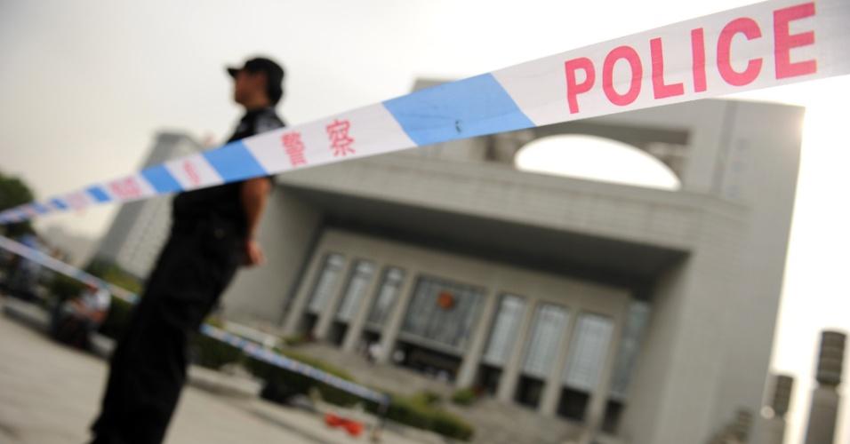 """20.ago.2012 - Policial é visto na porta na porta de tribunal onde Gu Kalai foi julgada em Hefei, na China, nesta segunda-feira (20). A mulher do ex-dirigente comunista chinês Bo Xilai foi considerada culpada pelo assassinato do empresário britânico Neil Heywood. No entanto, sua pena de morte foi """"suspensa"""". Ou seja, ela não será executada se tiver bom comportamento, ainda que, provavelmente, tenha que passar todo o resto da vida na prisão"""