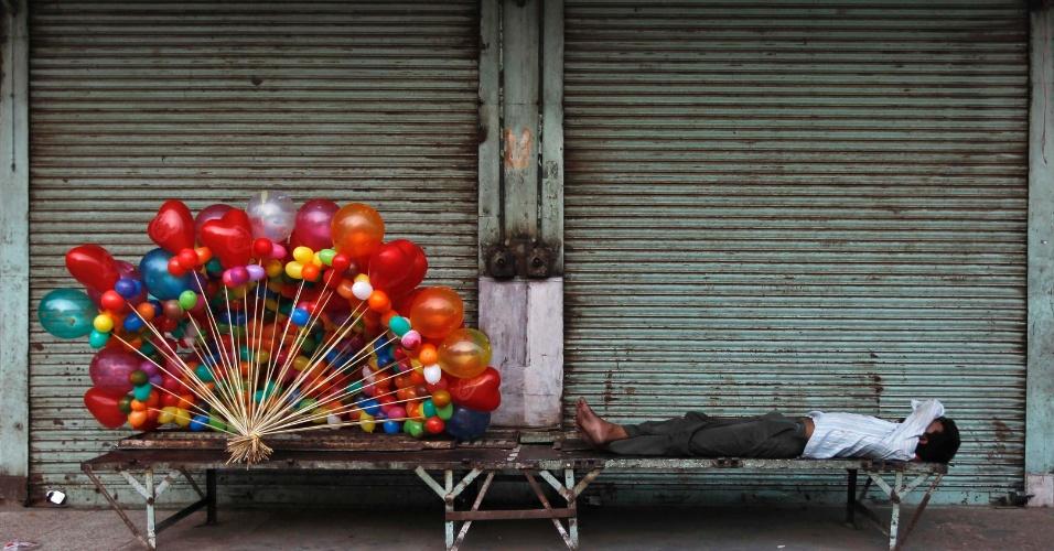 20.ago.2012 - Vendedor de balões descansa em um banco no centro de Nova Déli, na Índia