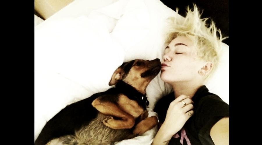 Muiley Cyrus divulgou imagem onde aparece dando um beijo em seu cachorro (20/8/12)