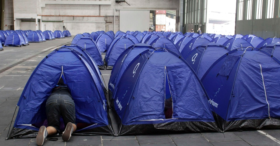 Homem entra em uma das milhares de tendas montadas para quem acampa na evento, realizado durante seis dias na cidade de Berlim, Alemanha