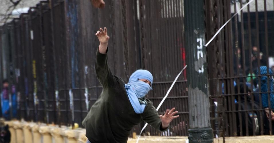 23.ago.2012 - Estudante chileno ataca pedra contra a polícia. Os manifestantes adotaram nova estratégia para exigir uma educação melhor: fizeram várias marchas simultâneas em diferentes bairros de Santiago, mas os protestos terminaram em confrontos com a polícia. Há mais de um ano, alunos têm feito manifestações para pedir mudanças na política educacional do país