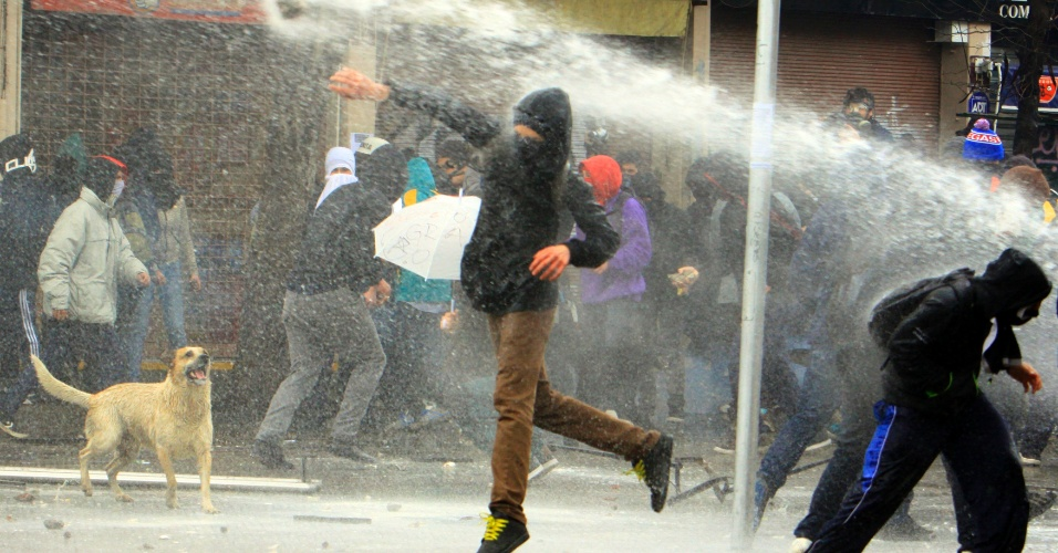 23.ago.2012 - Estudantes chilenos jogam pedras contra a polícia durante protesto em Santiago. Os manifestantes adotaram nova estratégia para exigir uma educação melhor: fizeram várias marchas simultâneas em diferentes bairros de Santiago, no Chile, mas os protestos terminaram em confrontos com a polícia. Há mais de um ano, alunos têm feito manifestações para pedir mudanças na política educacional do país