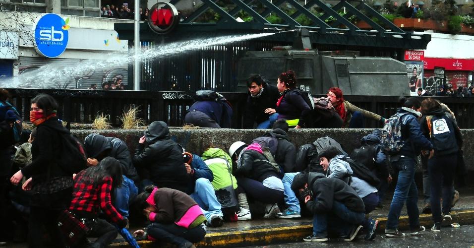 23.ago.2012 - Estudantes chilenos tentam se proteger de um caminhão com canhão de água da polícia. Os manifestantes adotaram nova estratégia para exigir uma educação melhor: fizeram várias marchas simultâneas em diferentes bairros de Santiago, no Chile, mas os protestos terminaram em confrontos com a polícia. Há mais de um ano, alunos têm feito manifestações para pedir mudanças na política educacional do país
