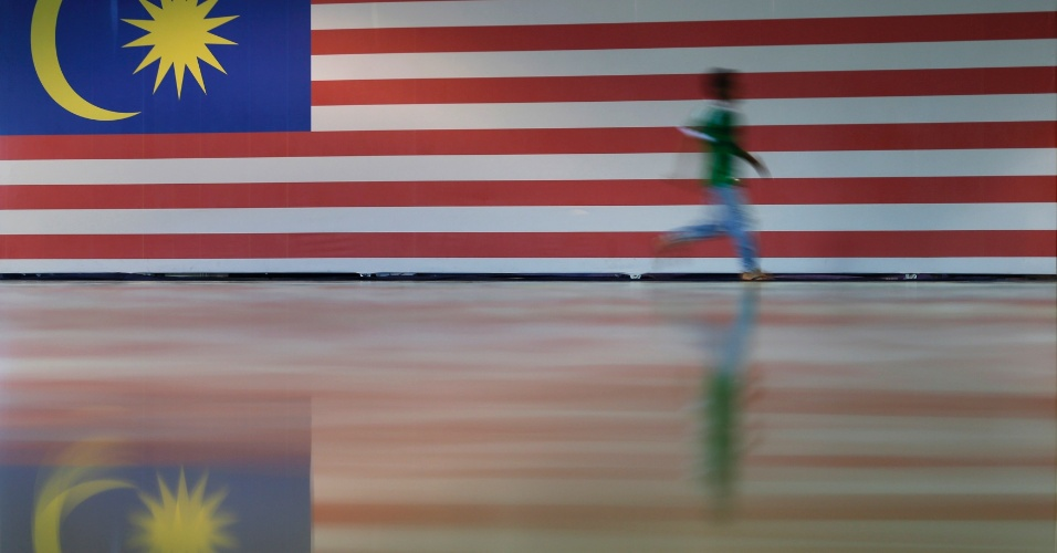 24.ago.2012 - Homem passa correndo nesta sexta-feira (24) por bandeira gigante da Malásia, preparada para a comemoração do Dia da Independência do país, em Kuala Lumpur. Malásia comemora 55 anos de independência em 31 de agosto