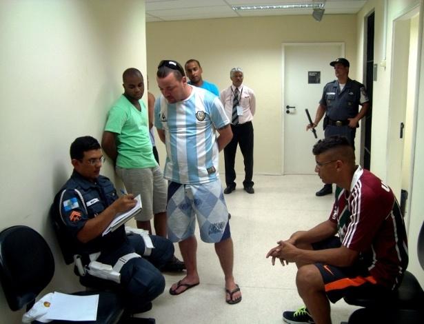 Policial militar confere documento de torcedores do Fluminense presos após briga