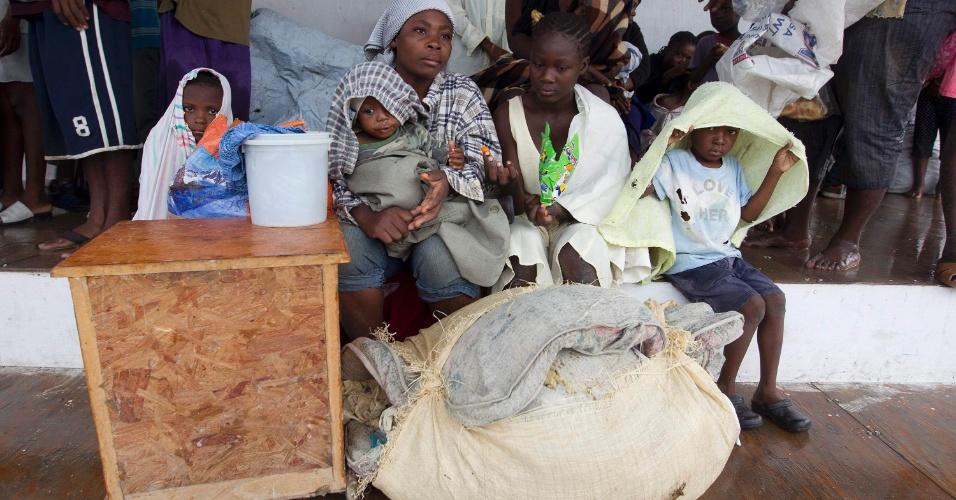 25.ago.2012 - Família segura seus pertences após fugir de casa que foi inundada pela tempestade Isaac, em Porto Príncipe (Haiti)