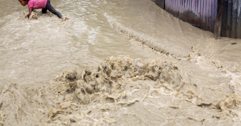 25.ago.2012 - Menina tenta atravessar rua inundada após tempestade tropical Isaac em Vicente Nobre, na República Dominicana