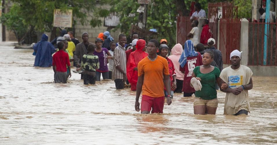 25.ago.2012 - Moradores de uma área baixa de Porto Príncipe, no Haiti, deixam suas casas que foram inundadas pela água durante a tempestade tropical Isaac