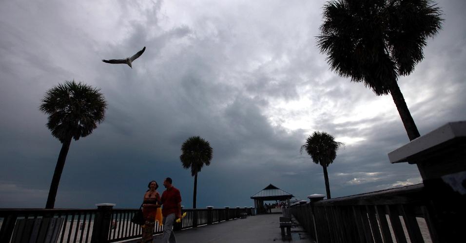 25.ago.2012 - Turistas caminham ao longo do cais de Clearwater, na Flórida. Moradores da párea de Tanoa esperam a chegada da tempestade tropical Isaac, que já fez estragos no Haiti, República Dominicana e Cuba