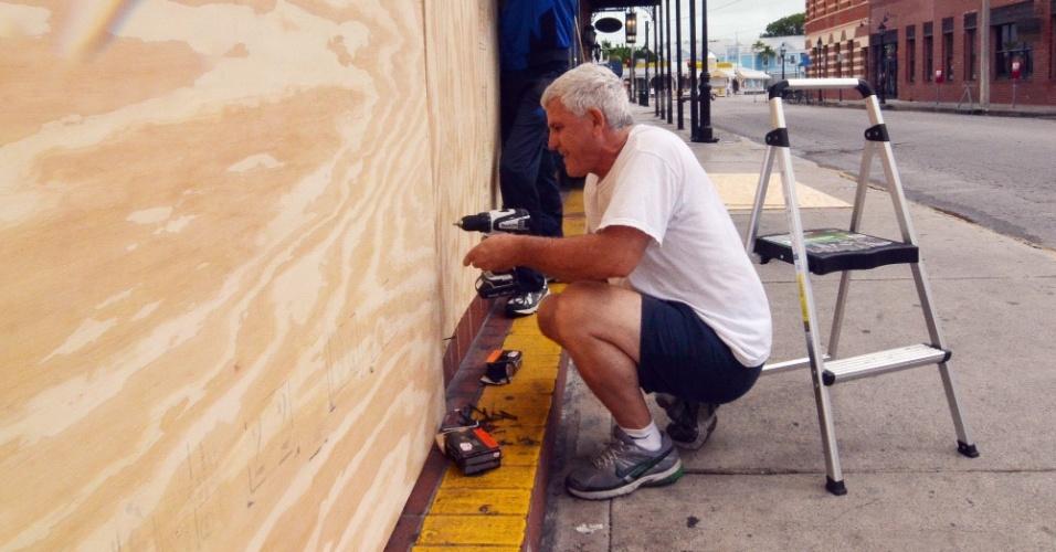 26.ago.2012 - Homem reforça a fachada de sua casa em Key West, na Flórida (Estados Unidos). A região está em estado de alerta em função da proximidade da tempestade tropical Isaac. O fenômeno meteorológico já atingiu Haiti, República Dominicana e Cuba