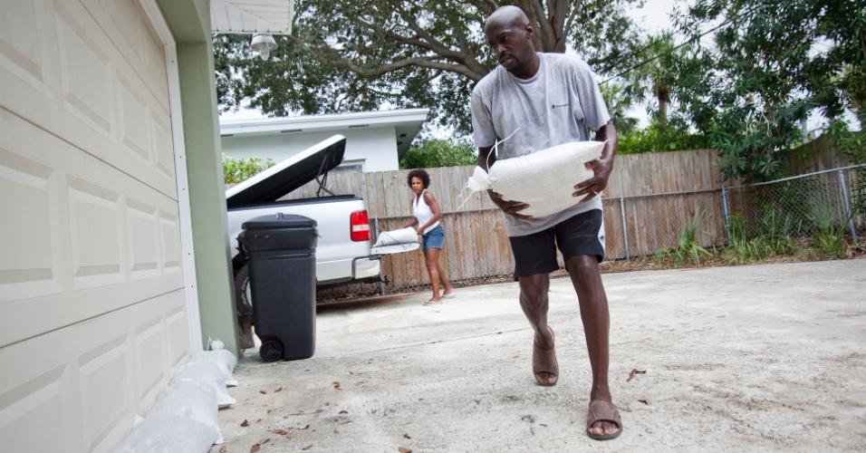 26.ago.2012 - Os americanos Earl (direita) e Terri Harris (esquerda) preparam a casa para uma possível inundação de água em função da tempestade tropical Isaac, que se aproxima da região da Flórida