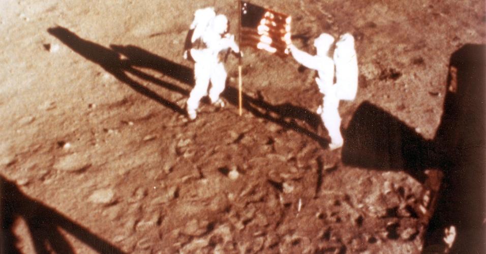 Os astronautas Neil Armstrong e Aldrin colocam a bandeira americana na superfície lunar durante a missão Apollo 11