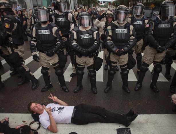 27.ago.2012 - Ativista deita em frente a policiais durante protesto nas ruas de Tampa, na Flórida (EUA), contra a realização da Convenção Nacional do Partido Republicano, na qual o ex-governador Mitt Romney será nomeado candidato à Presidência dos Estados Unidos