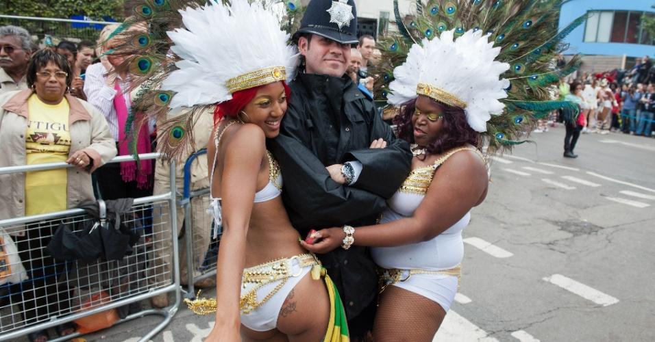 27.ago.2012 - Foliãs brincam com guarda durante o festival de Notting Hill, que leva milhões de pessoas às ruas, em Londres. O evento, inspirado em festas do Caribe, é considerado o maior carnaval de rua da Europa