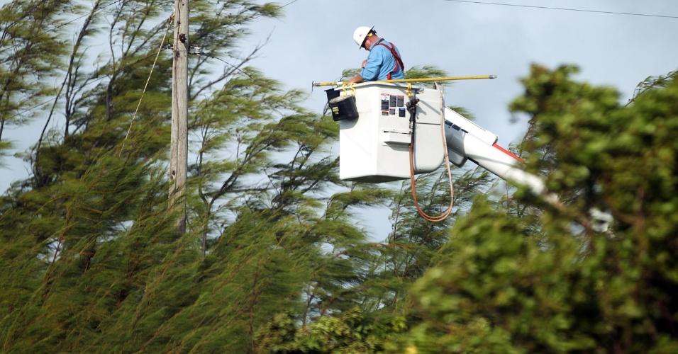27.ago.2012 - Funcionário da companhia de energia tenta religar os cabos que foram danificados após a passagem da tempestade tropical Isaac, em Key West, cidade da Flória, nos EUA