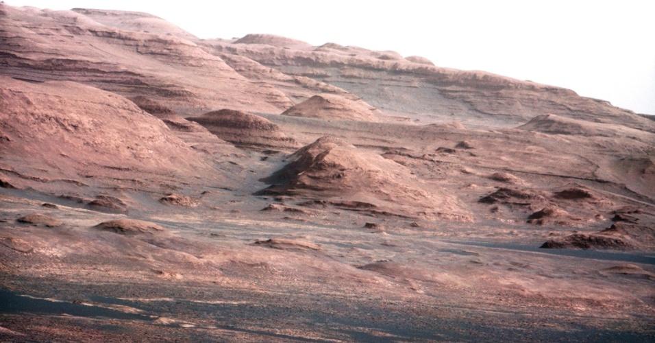 27.ago.2012 - Imagem divulgada pela Nasa nesta segunda-feira (27) mostra o Monte Sharp, destino final do robô Curiosity, que se encontra em Marte. As partes mais baixas do monte formam uma sucessão de estratos tão espessos como os do Grand Canyon, nos EUA. A principal diferença é que os estratos do Grand Canyon são expostos ao longo de um grande vale, enquanto os estratos do Monte Sharp são expostos ao longo dos flancos de uma grande montanha. A foto, que mostra a diversidade de cores do monte, foi tirada pelo Curiosity