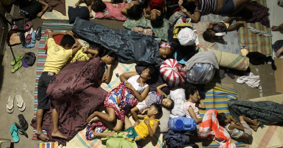 27.ago.2012 - Moradores da cidade de Muntinlupa, no sul de Manila, nas Filipinas, descansam em um dos centros de evacuação montado para receber os desabrigados devido às fortes chuvas. Os temporais já provocaram a destruição de centenas de moradias e inundaram mais de 60% da capital filipina