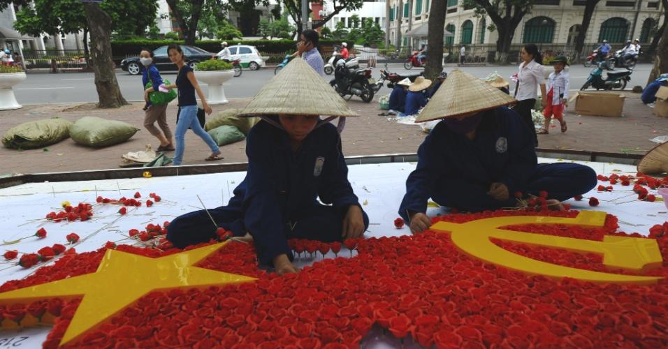 27.ago.2012 - Moradores de Hanói, no Vietnã, preparam uma bandeira feita com flores para decorar uma das praças no centro da cidade, no dia 2 de setembro, quando se comemora o Dia da Independência do Vietnã
