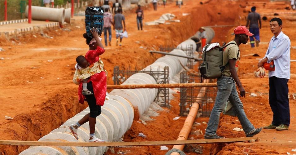 27.ago.2012 - Trabalhador chinês cruza ponte improvisada em Viana, cidade localizada na região de Luanda, em Angola