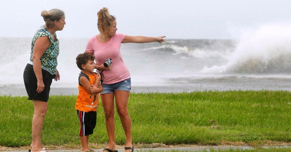 28.ago.2012 - Família assiste às ondas arrebentarem na costa de Lake Pontchartrain, enquanto o furacão Isaac aproxima-se de Nova Orleans, no estado de Louisiana, nos EUA